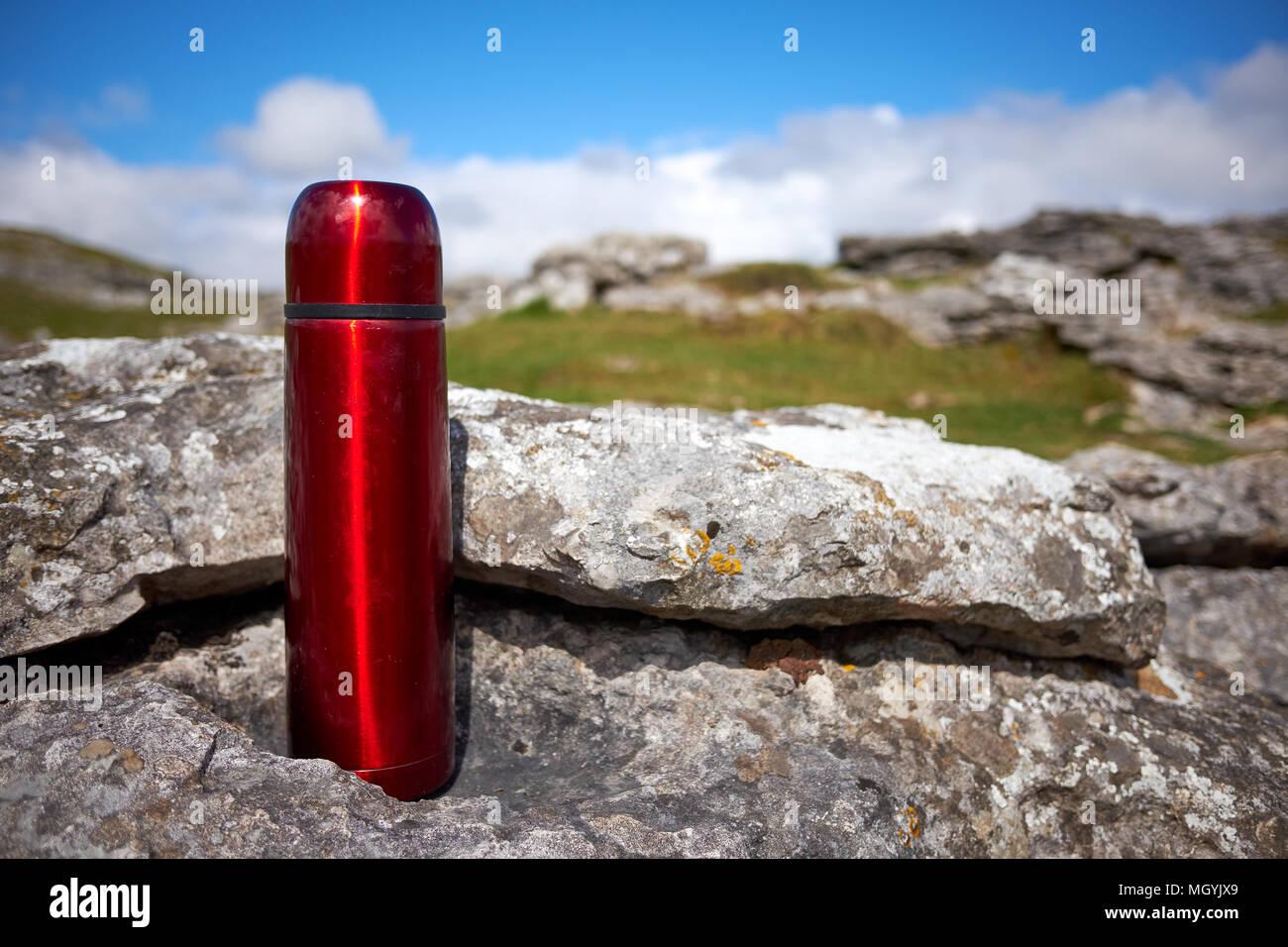 Eine rote Thermoskanne für heiße Getränke ruht auf einem Kalkstein ...