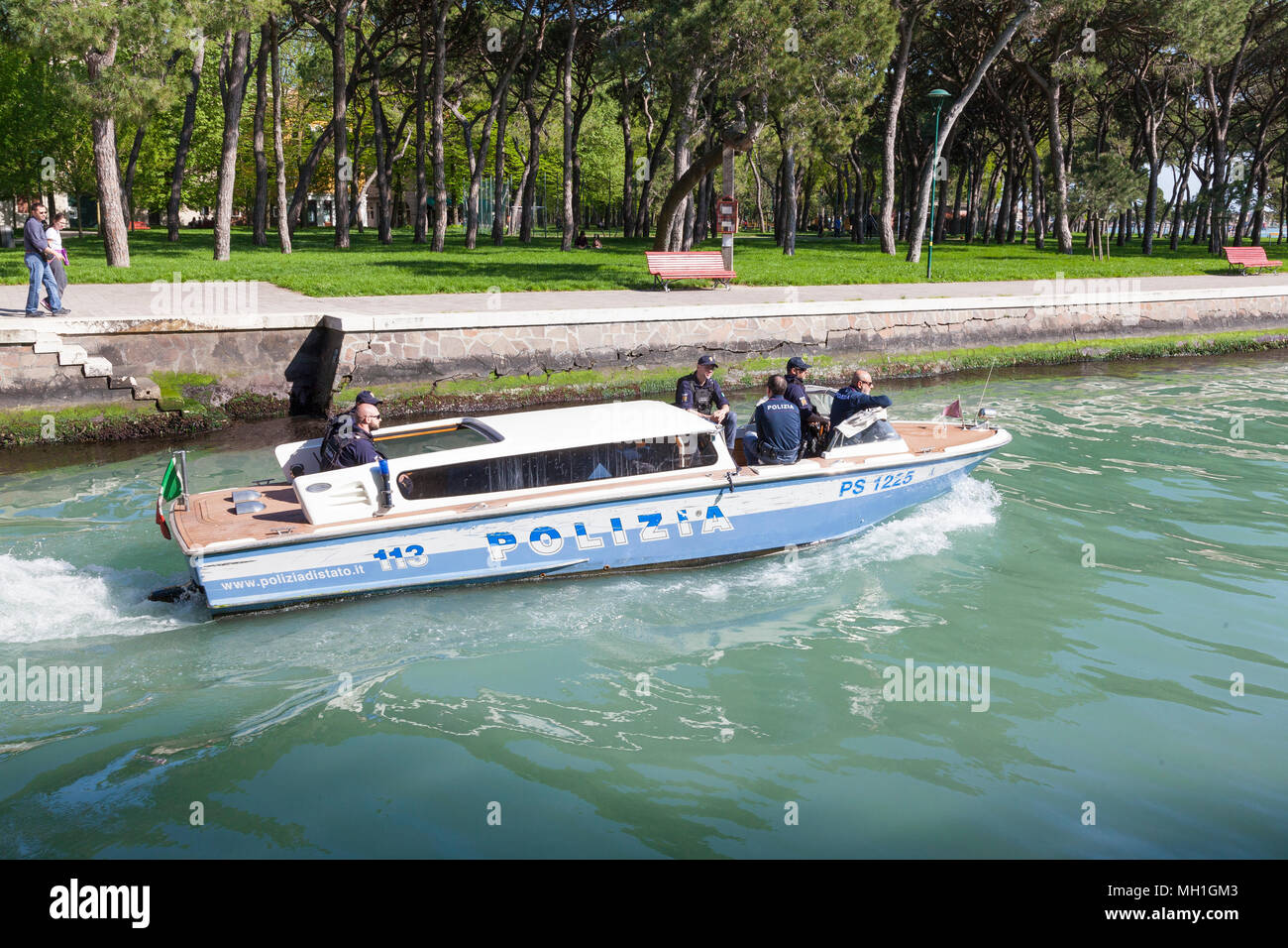 Italienischen Polizia patrol Boot auf dem Rio del Giardini, Castello, Venice, Italien mit einem Team von Polizisten, Paar beobachtet sie Pass und Sant'Elena beh Stockbild