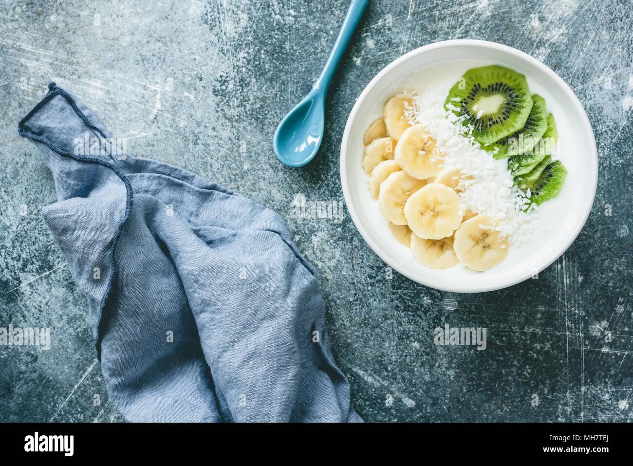 Joghurt mit Banane, Kiwi, Kokos Schüssel. Vegan Joghurt mit Früchten. Gesunde Ernährung, Diät, Fitness, gesunde Lebensweise Konzept. Tabelle Ansicht von oben Stockbild