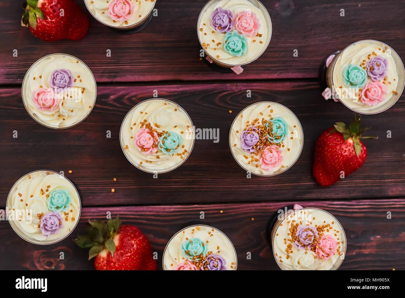 Kuchen mit Erdbeeren im Glas serviert, Schüsse, Holz- Hintergrund Stockbild