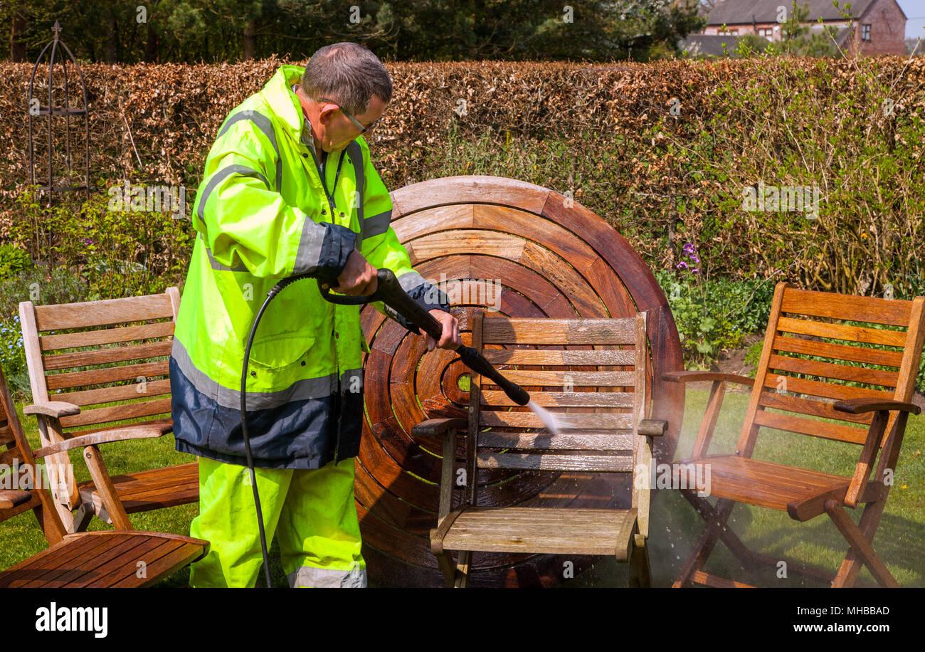 Mann, gut sichtbare Kleidung und Berufsbekleidung Reinigung hartholz Gartenmöbeln aus Holz mit einem Power/Jet Unterlegscheibe Stockfoto