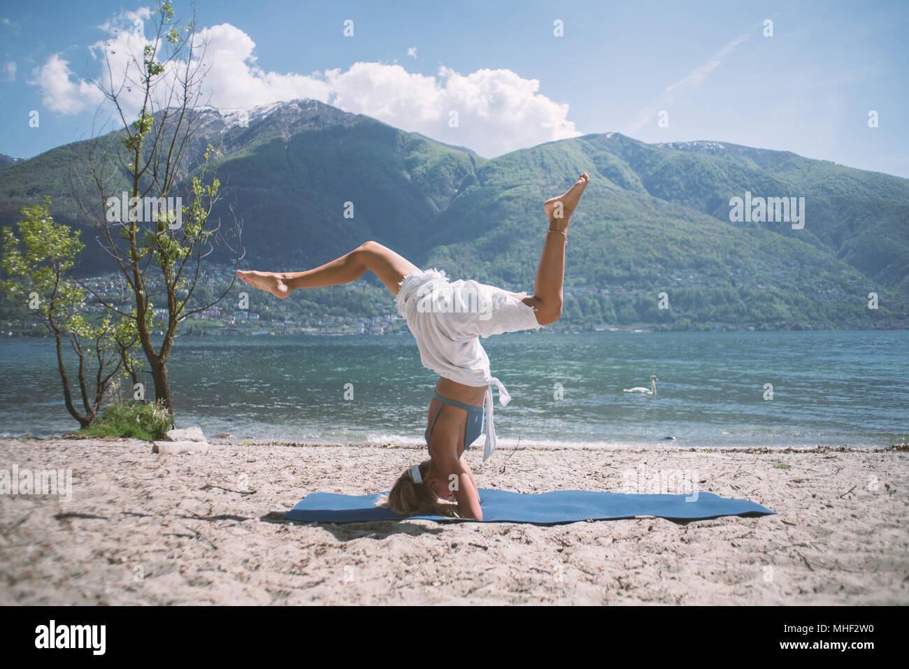Junge Frau trainieren Yoga durch den See und die Berge, im Kanton Tessin, Schweiz, Europa erschossen. Menschen Entspannung Wohlbefinden Konzept Stockbild