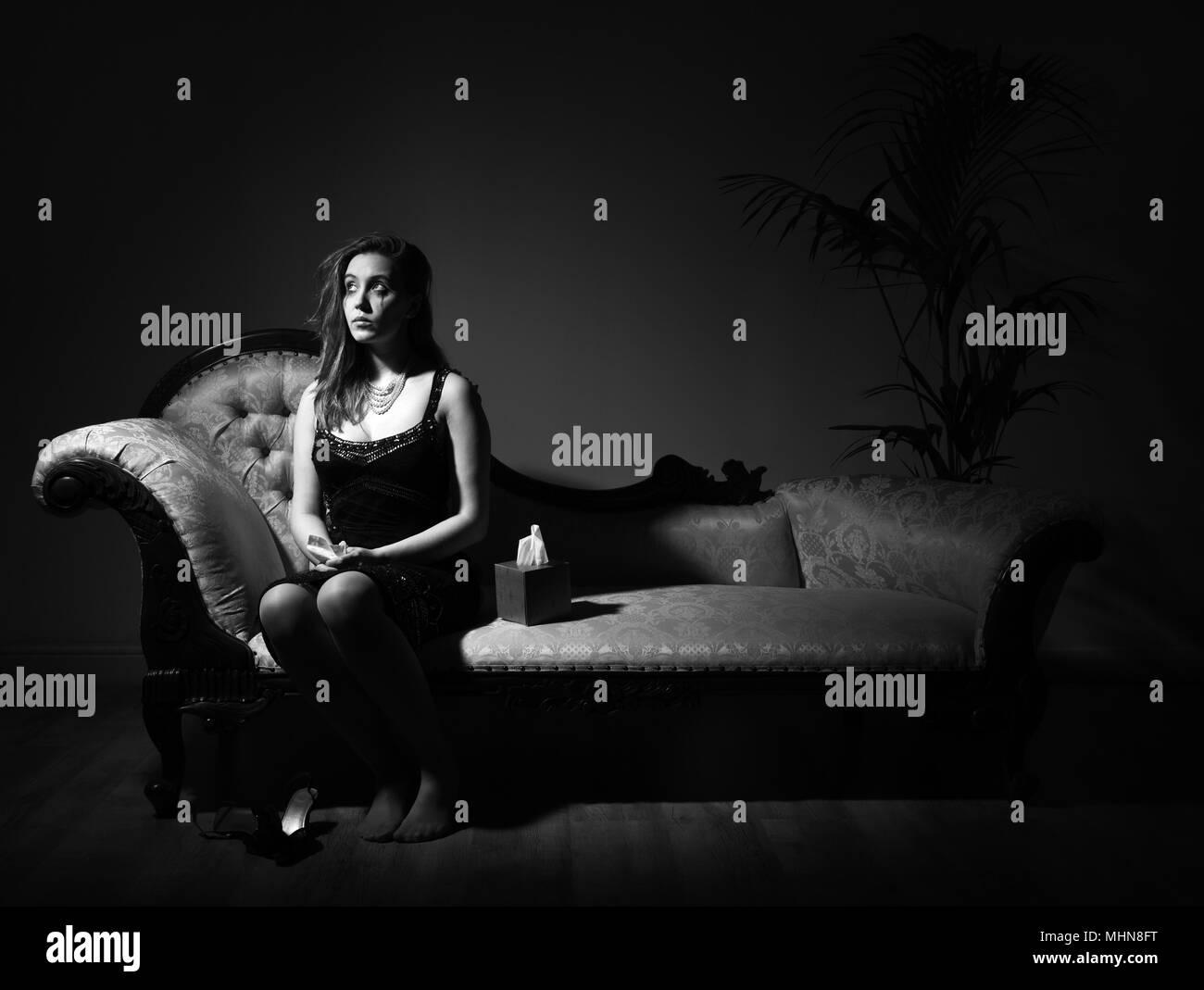 Frau im Abendkleid sitzen auf einer Chaiselongue, weinen Stockbild