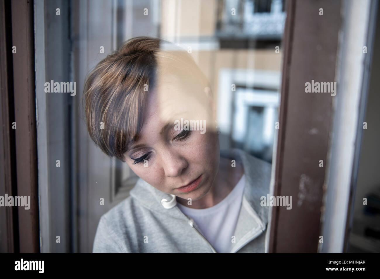 Junge schöne depressiv unglücklich kaukasische Frau besorgt und traurig durch das Fenster zu Hause. Gefühl, wertlos und Schmerzen. closeup. Depressi Stockbild