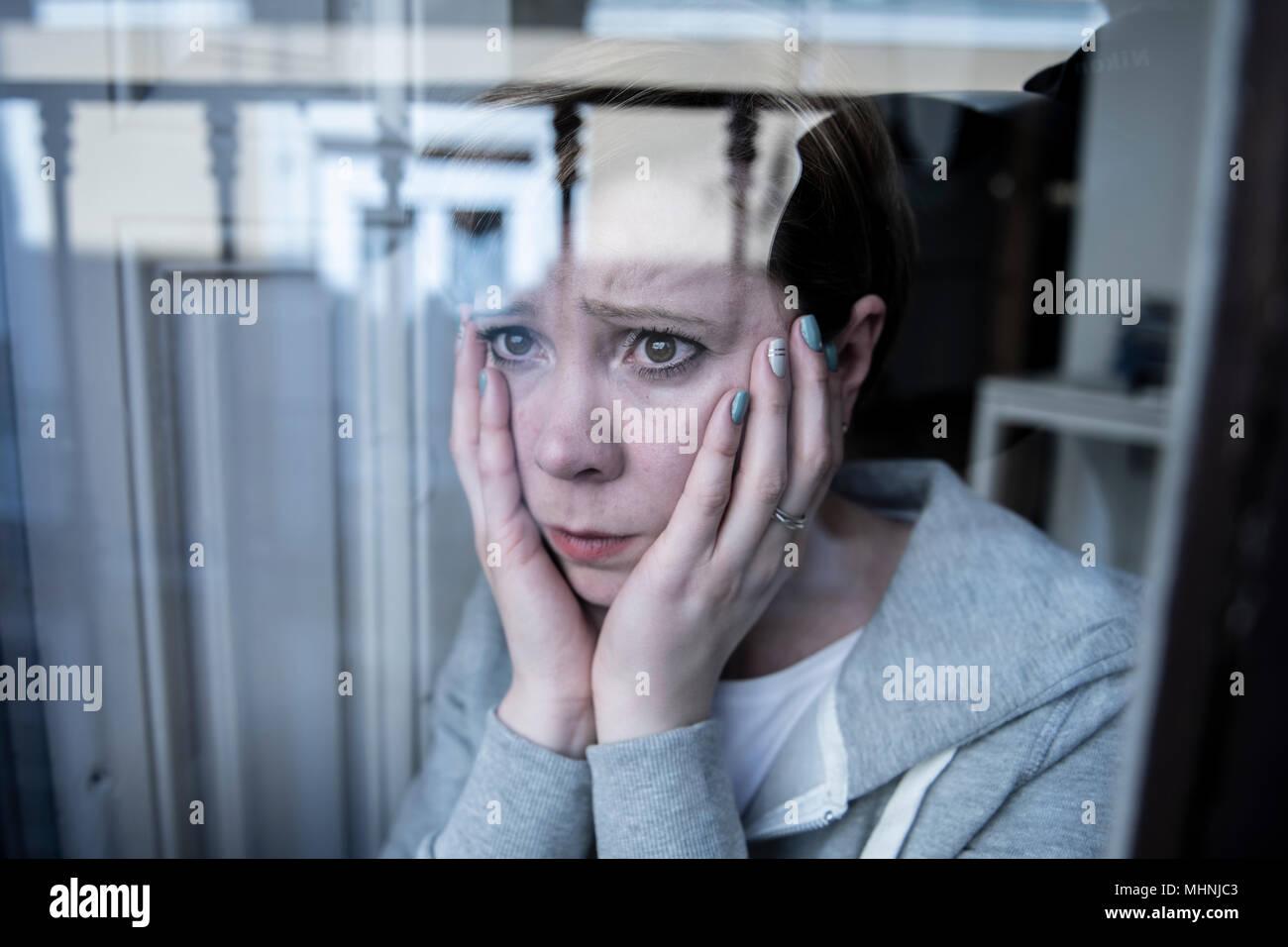Junge schöne depressiv unglücklich kaukasische Frau besorgt und traurig durch das Fenster zu Hause. Gefühl, wertlos und Schmerzen. closeup. Depressi Stockfoto