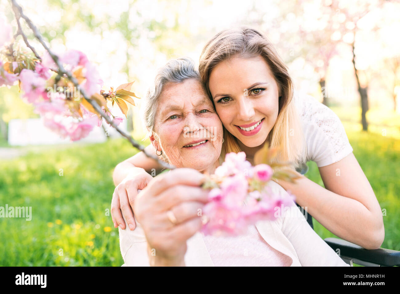 Ältere Großmutter im Rollstuhl mit Enkelin im Frühjahr die Natur. Stockbild