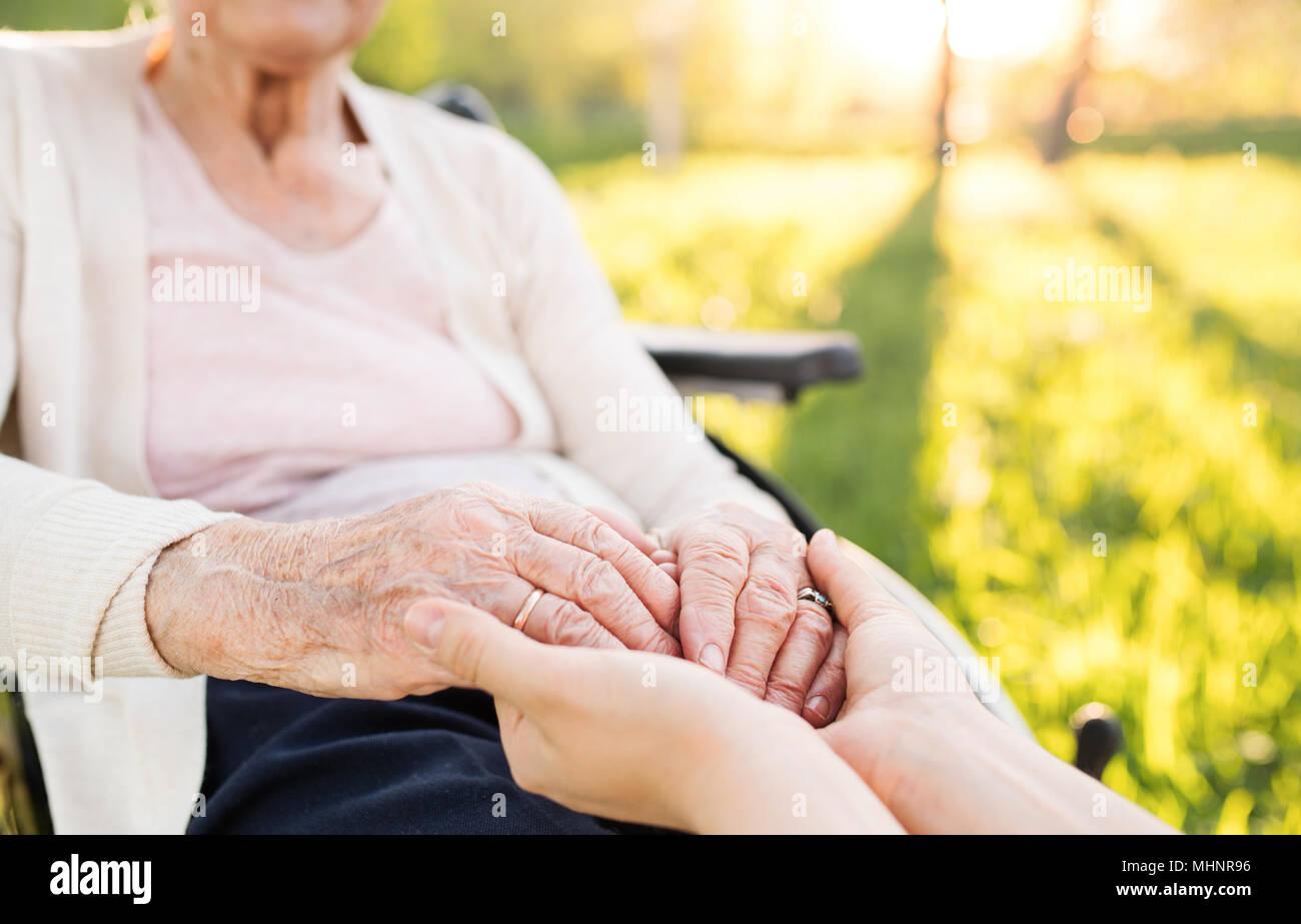 Ältere Großmutter im Rollstuhl mit Enkelin im Frühjahr die Natur. Stockfoto