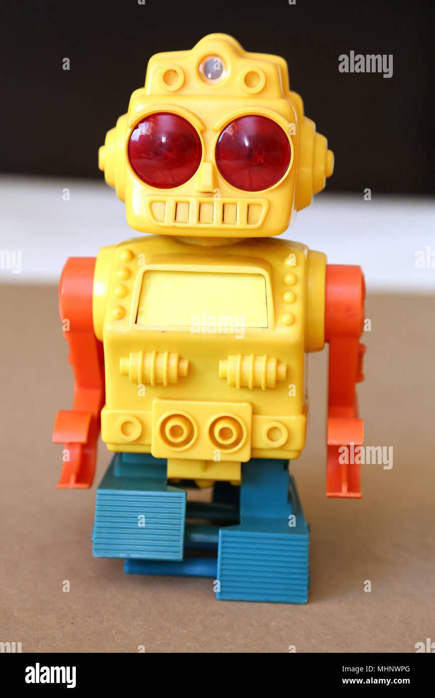 Retro Spielzeug zu Fuß Kunststoff Roboter mit gelben Körper, große rote Augen, Orange und Blau. Stockbild