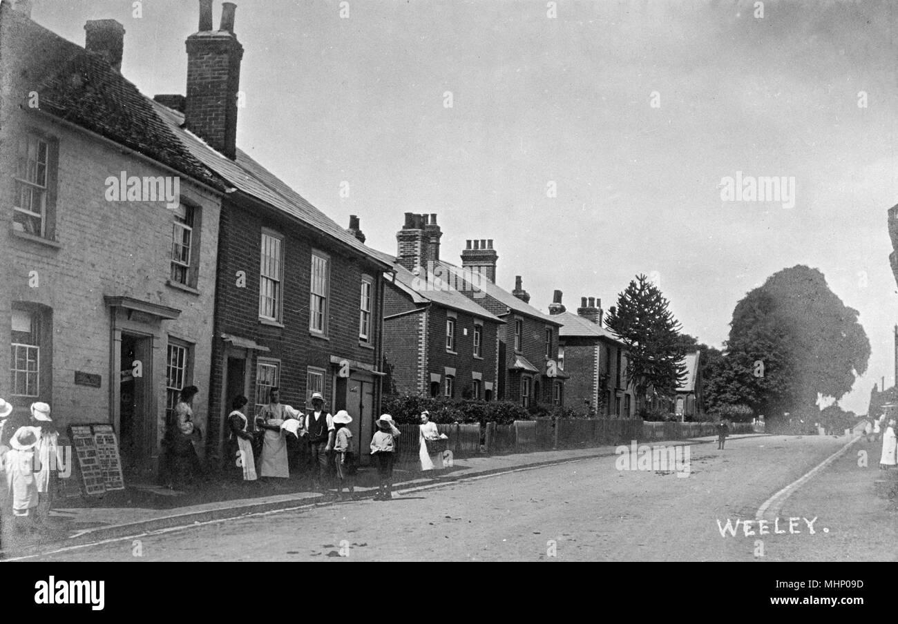 Straßenszene in der Ortschaft Weeley, Essex, mit einer Gruppe von Leuten auf der linken Seite. Datum: ca. 1910 s Stockbild