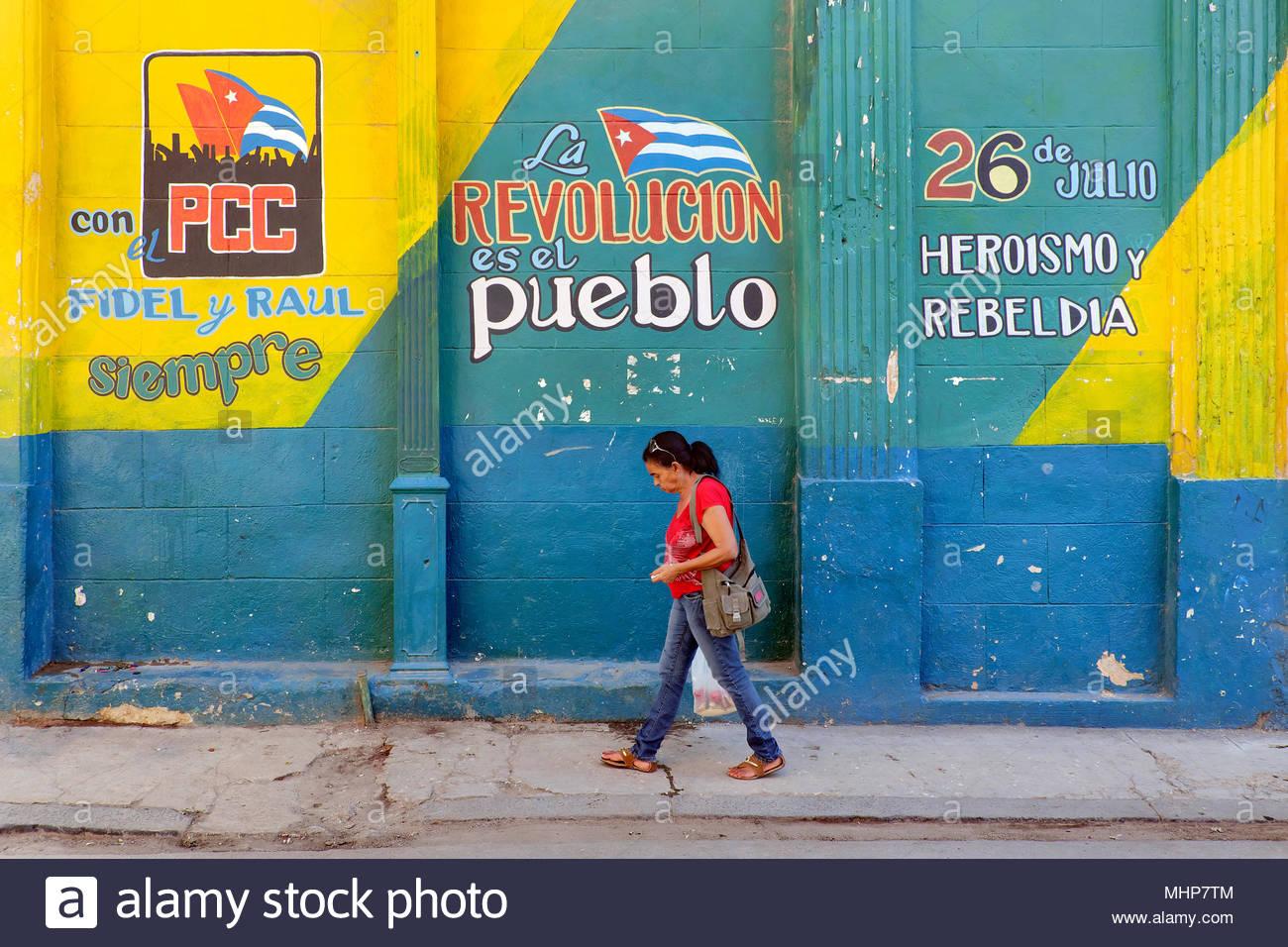 Frau übergibt eine bunte Wand mit politischen Graffiti, dass die Kubanische Revolution feiert am 26. Juli, Havanna, Kuba Stockbild