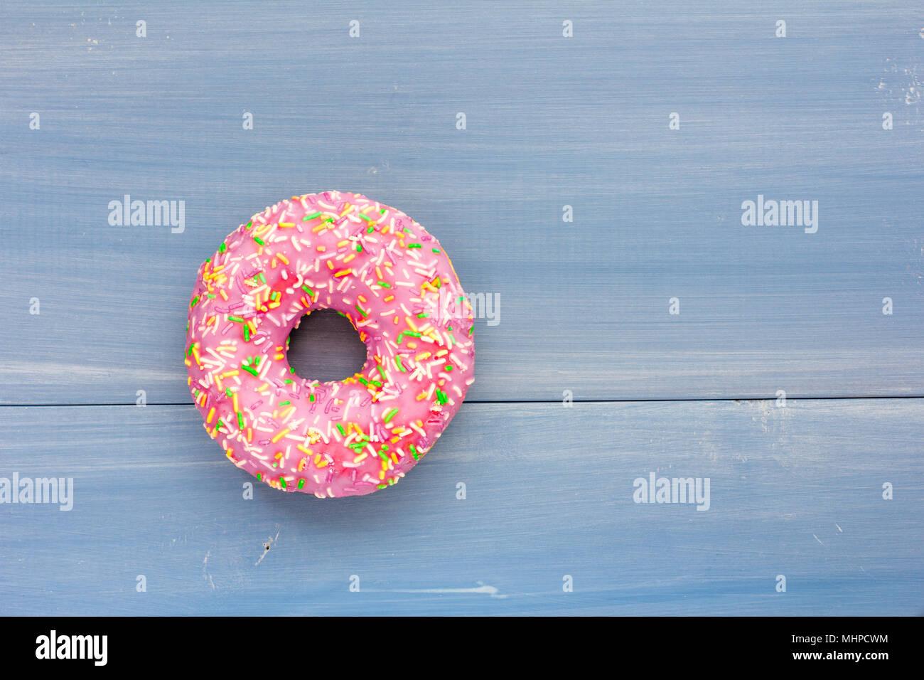 Eine einzelne Donut auf Blau Holz- Hintergrund Stockbild