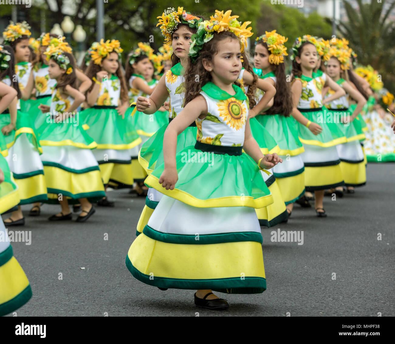 Funchal, Madeira, Portugal - April 22; 2018: Eine Gruppe von Mädchen in bunten Kleidern tanzen bei Madeira Blumenfest Parade in Funchal auf der Isla Stockbild