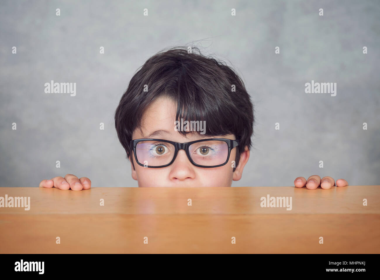 Junge mit Brille auf einem Holztisch auf grauem Hintergrund Stockbild