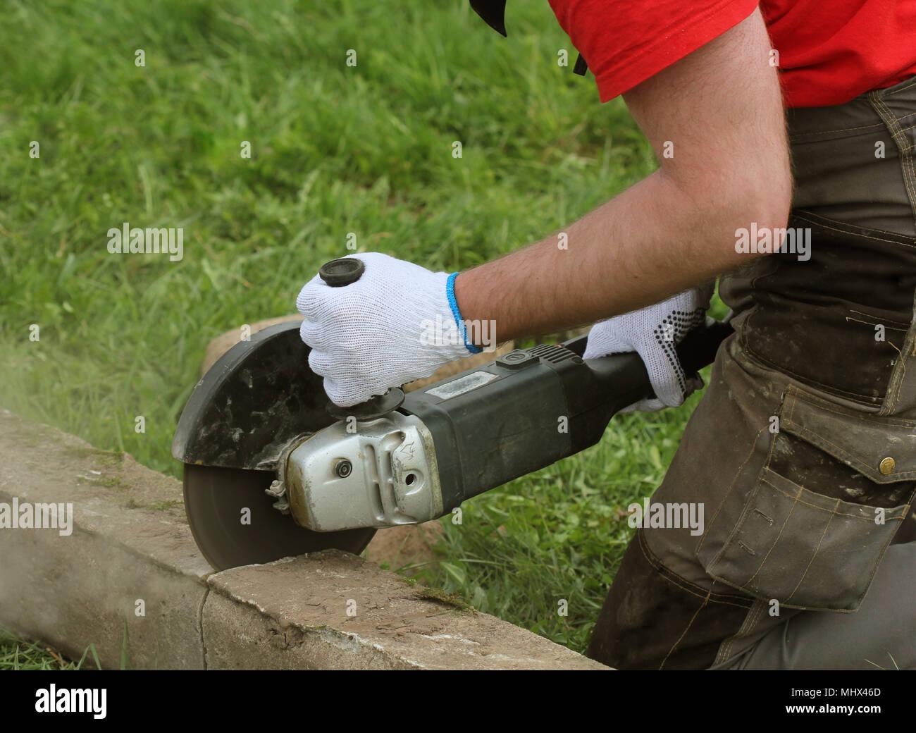 bauarbeiter schneiden betonplatte für zaun stiftung mit einem cut