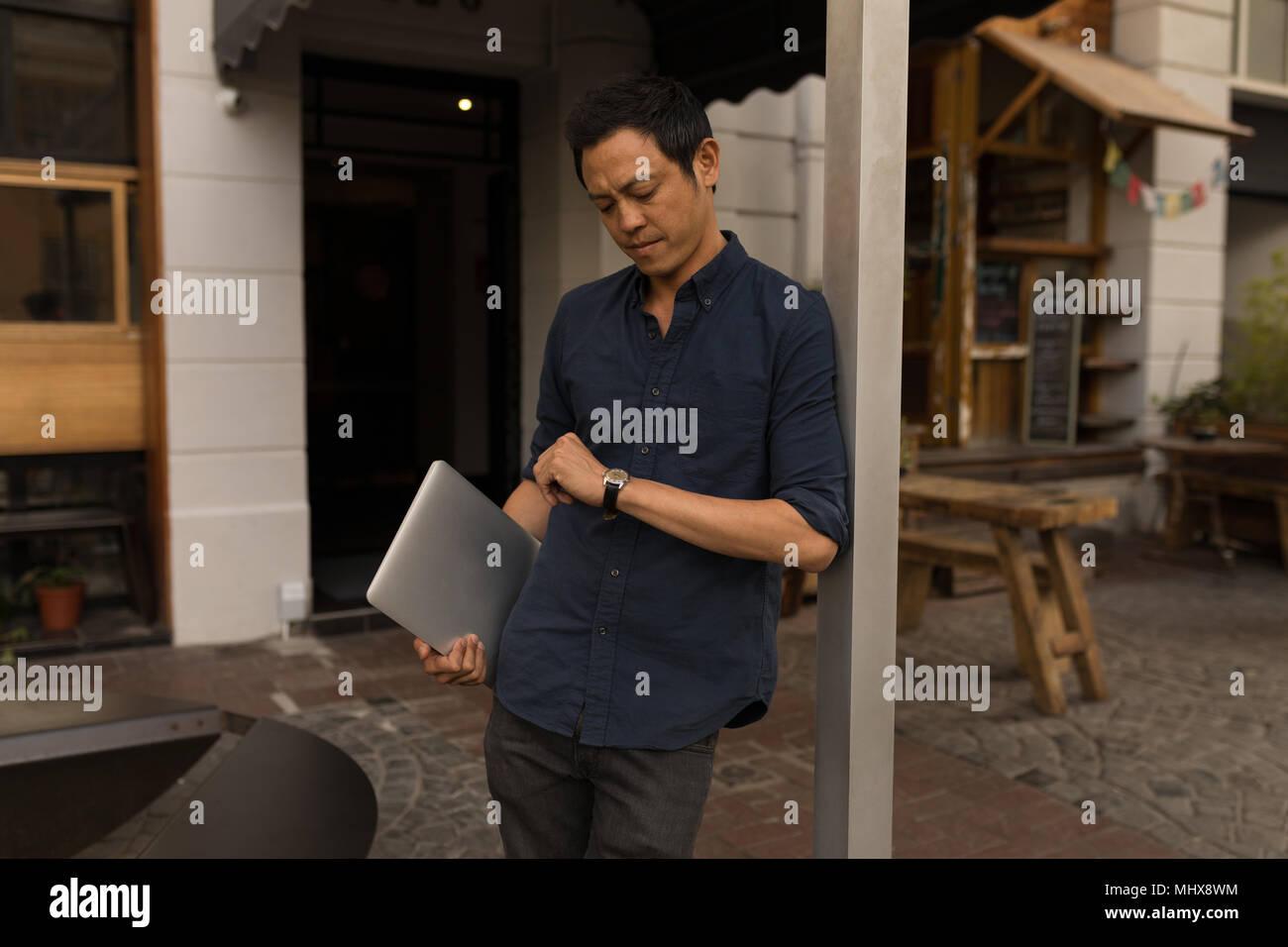 Geschäftsmann mit Laptop Kontrolle seiner Smartwatch Stockbild