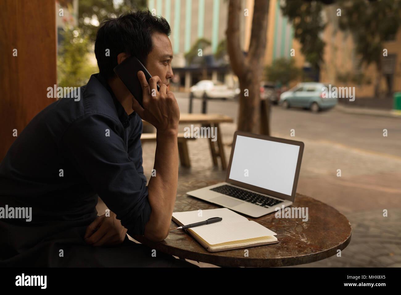 Unternehmer Gespräch am Handy im Cafe Stockbild