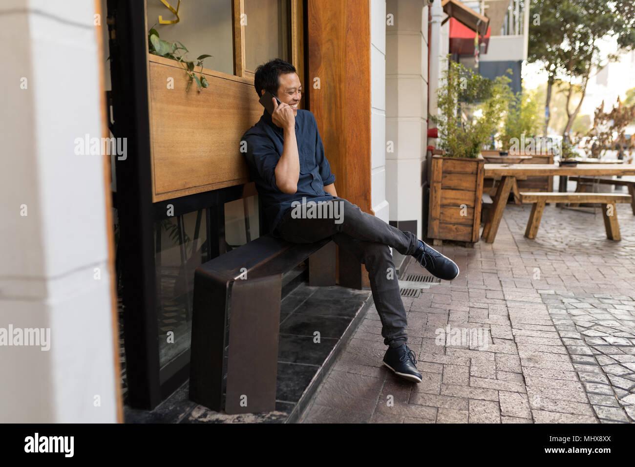 Geschäftsmann am Telefon sprechen im Straßencafé Stockbild