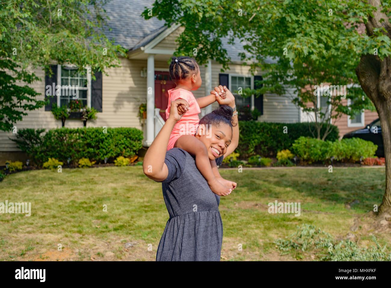 Mitte der erwachsenen Frau im Garten, die kleine Tochter auf den Schultern, Porträt Stockbild