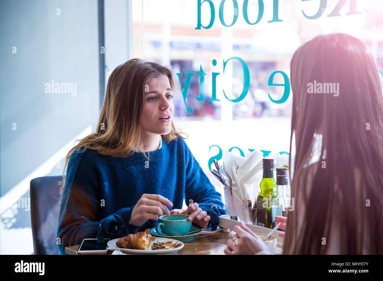 Zwei weibliche Freunde sitzen zusammen im Café, Kaffee trinken Stockbild