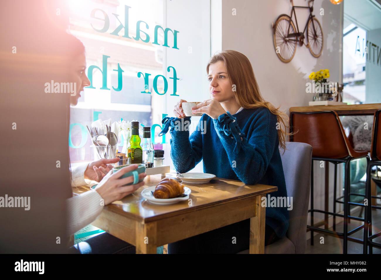 Zwei weibliche Freunde sitzen zusammen im Café, Kaffee trinken Stockfoto