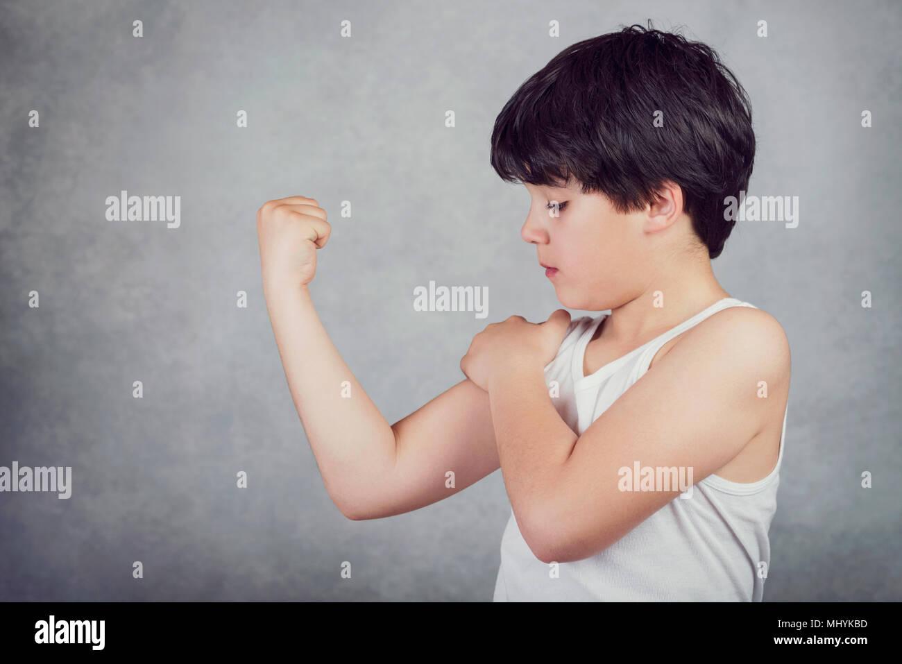 Kind seine Muskeln auf grauem Hintergrund angezeigt. Stockbild
