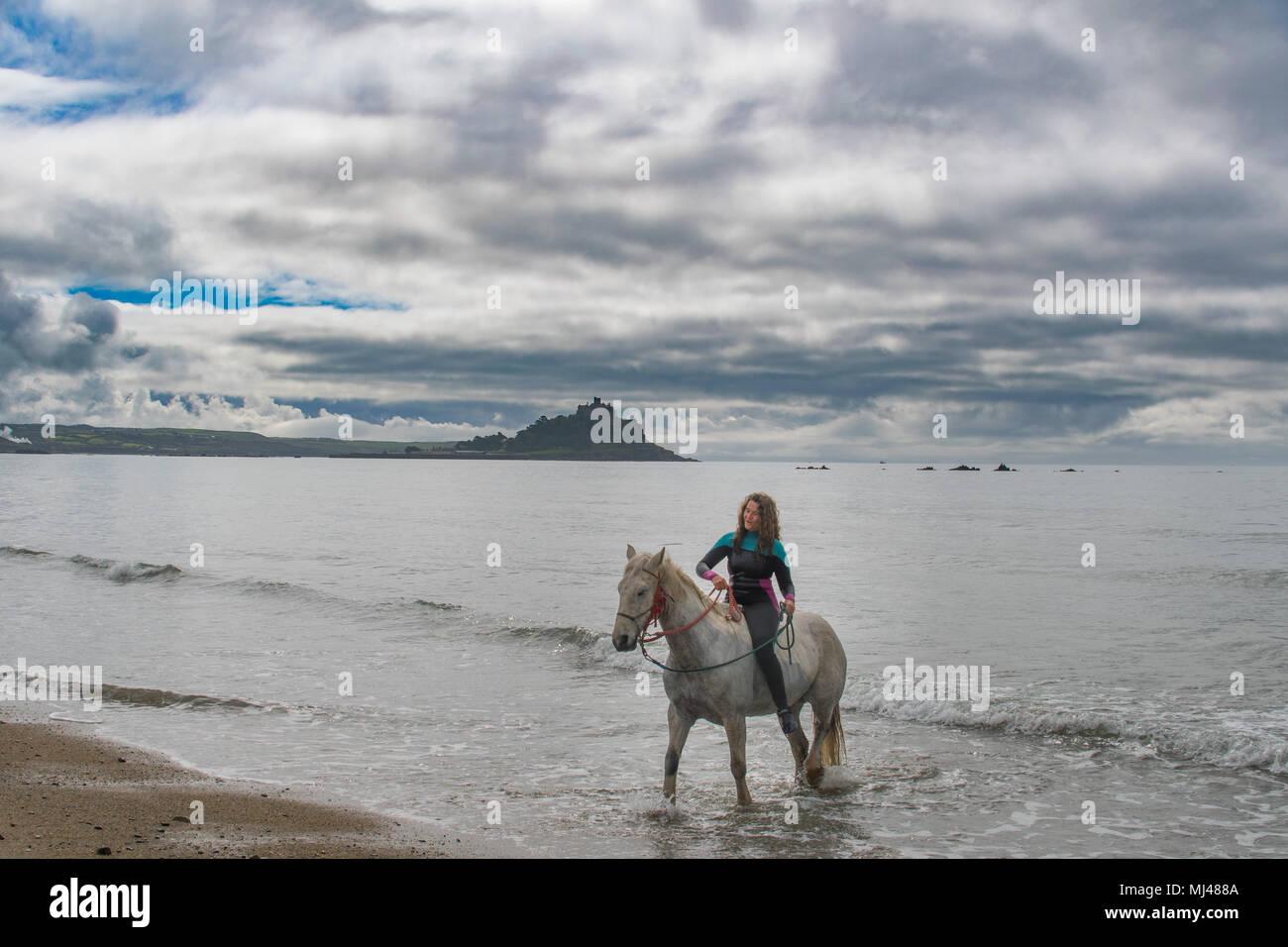 Pferde schwimmen im Meer bei langen Felsformation Cornwall, mit Reiter auf den Pferden. Stockbild