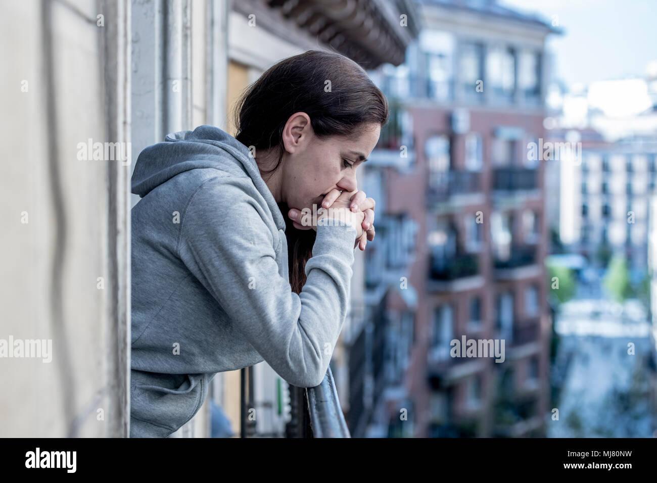 Junge Latein. traurig und deprimiert Frau, die auf einem Balkon Gefühl überwältigt und Leiden Depressionen in der psychischen Gesundheit Konzept Stockfoto