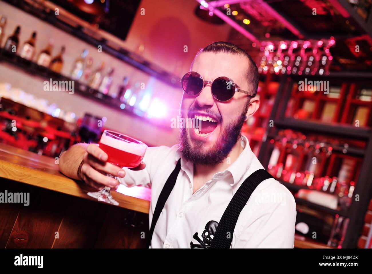 Netter Kerl in runde Sonnenbrille mit Cocktail Spaß auf bar Hintergrund Stockbild