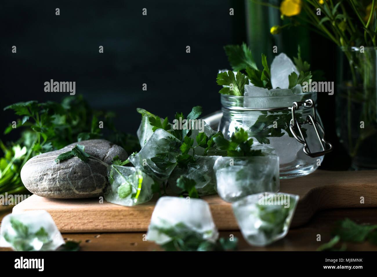 Eiswürfel mit tiefgekühlte Kräuter für Obst infundiert Wasser auf rustikalen Holzmöbeln Hintergrund Stockfoto