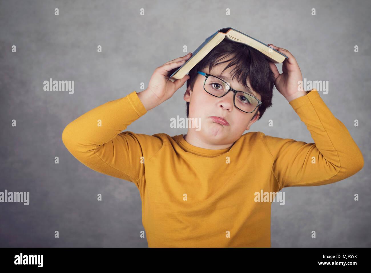 Traurige und nachdenkliche Junge mit einem Buch auf dem Kopf auf grauem Hintergrund Stockbild