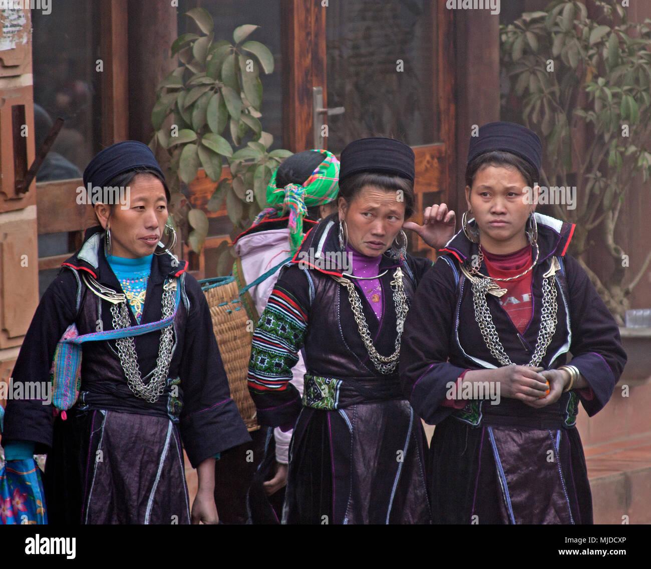 Reife asiatische Frau mit drei Schwarzen