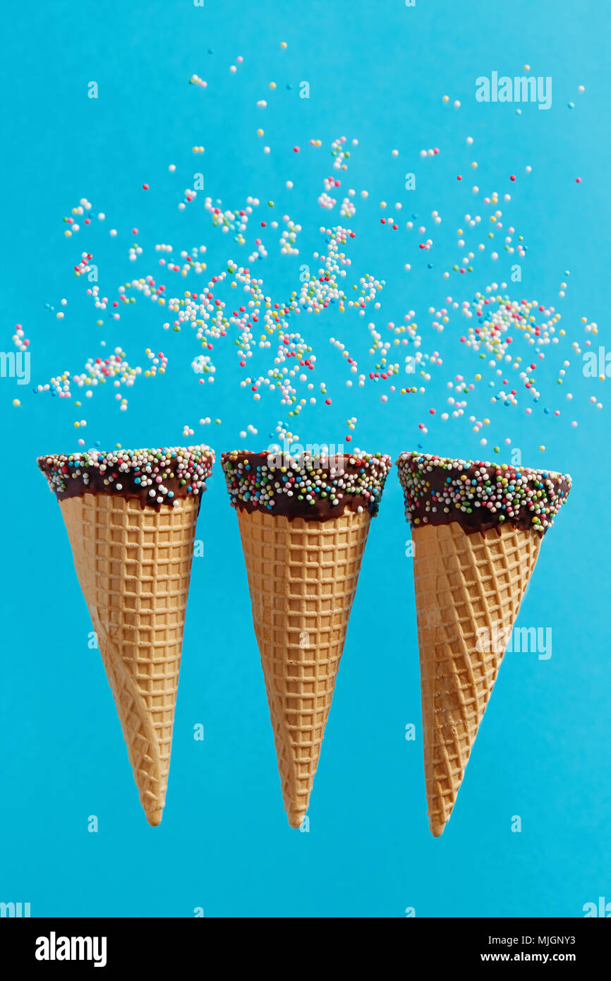 Eistüten mit bunten Streuseln auf blauem Hintergrund. Stockbild
