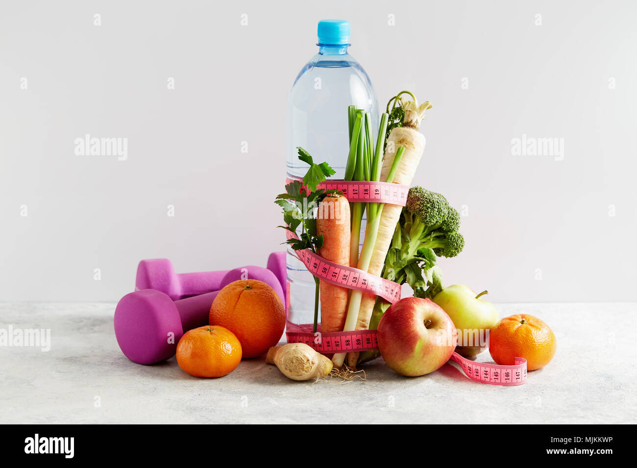 Flasche Wasser mit einem rosa Maßband, Gemüse und Obst. Konzept Gesundheit, Diät und Ernährung. Stockbild