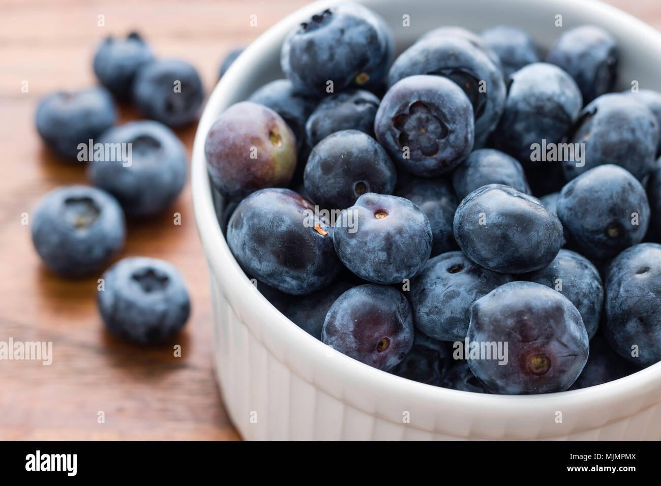 Kleine weiße Schüssel gefüllt mit frischen Blaubeeren, sechs Blaubeeren auf der linken Seite, Holzplatte Hintergrund, gesunde Ernährung Konzept Stockbild