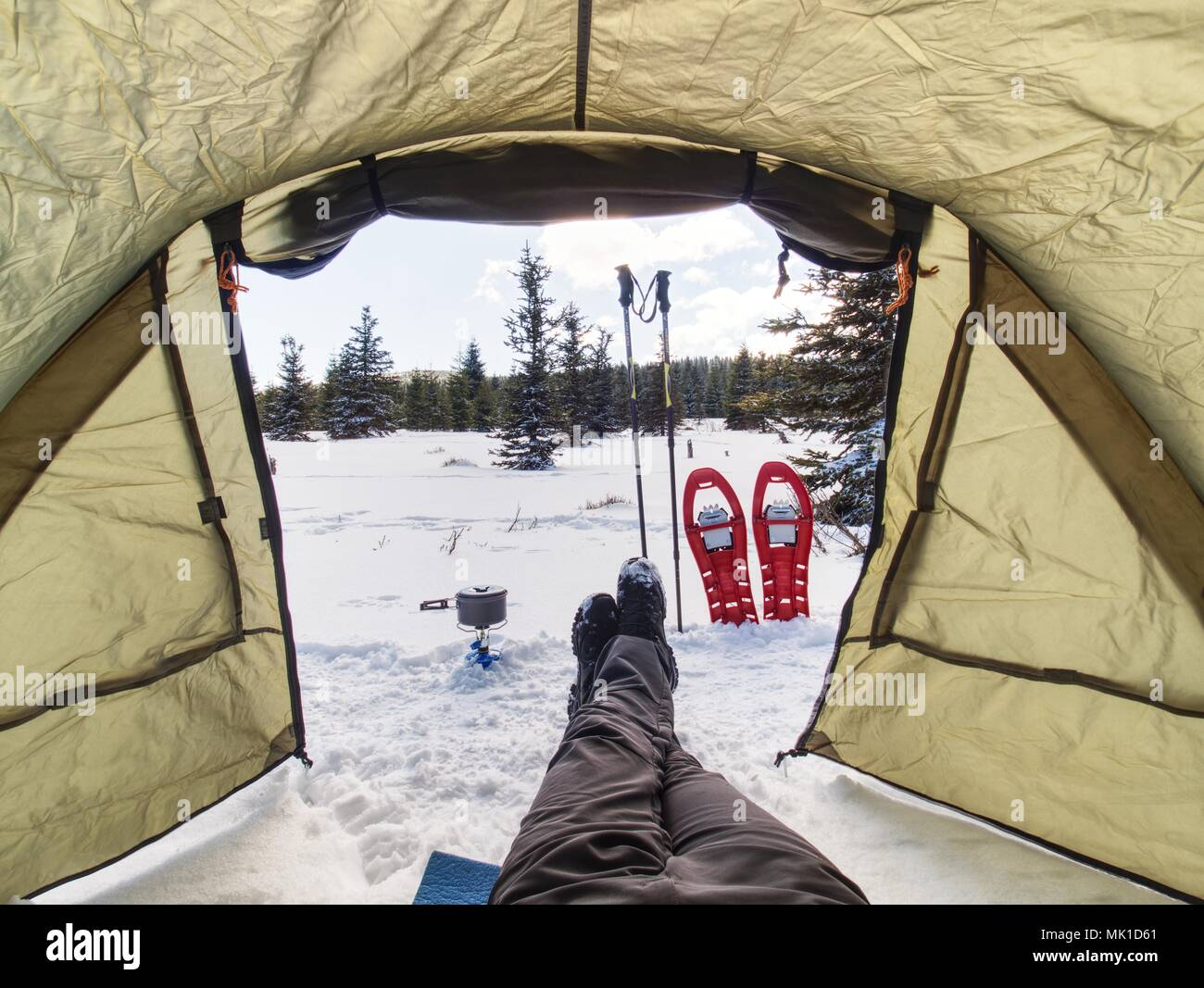 Kochen vor dem Zelt im Schnee. Wanderer Camping im Winter Berge. Mann Kochen mit portablen Gaskocher und leichte Gerichte. Brennendes Gas Herd ein Stockbild