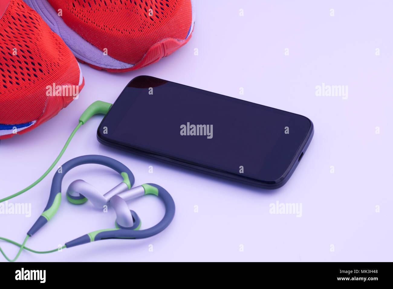 f5595de24b6628 Lebhaften orange Lauftraining Schuhe mit schwarzen handy handys mit grün  und silber grau Kopfhörer auf einem weißen Hintergrund. Laufen