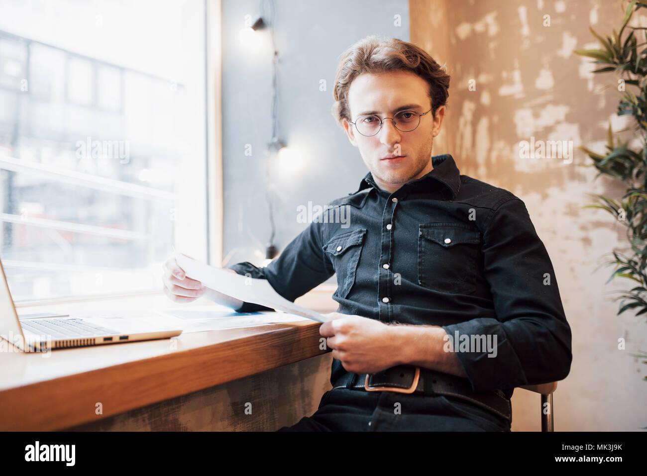 Entspannt Young Professional Surfen im Internet auf seinem Laptop in einem Café Stockbild