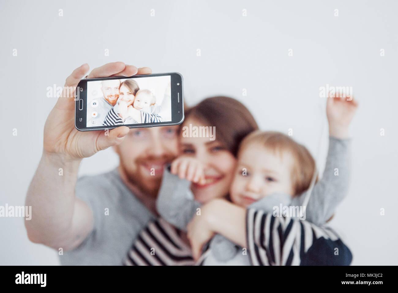 Familie, Feiertage, Technik und Mensch - lächelnd, Mutter, Vater und kleine Mädchen, selfie mit Kamera auf weißem Hintergrund Stockbild