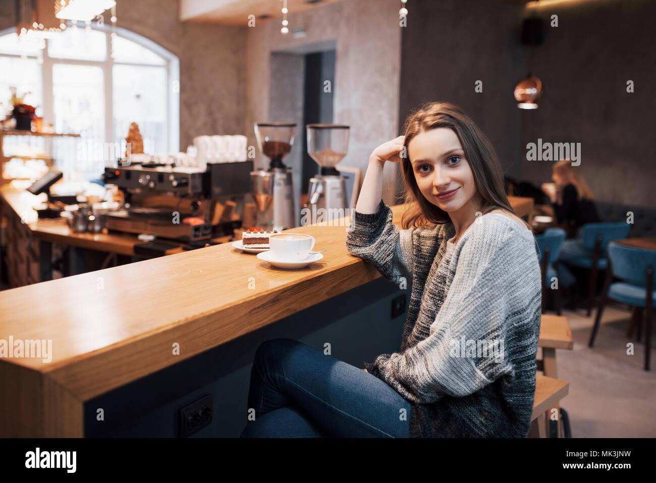 Attraktive junge Frau sitzt innen in städtischen Cafe. Cafe Stadt Lebensstil. Casual Portrait von jugendlichen Mädchen. Getönt. Stockbild