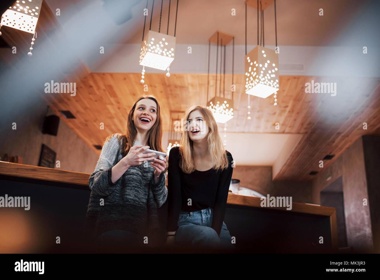 Kommunikation und Freundschaft Konzept - lächelnde junge Frauen mit Kaffeetassen im café Stockbild