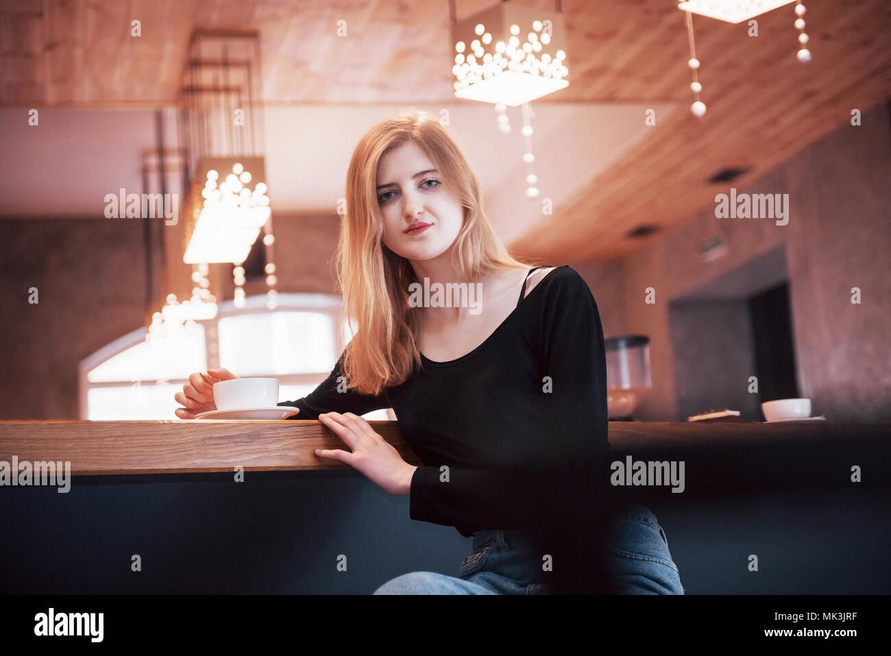 Glücklich lächelnde junge Frau mit Phone in einem Café. Schöne Mädchen in trendigen Frühling Farben Stockbild
