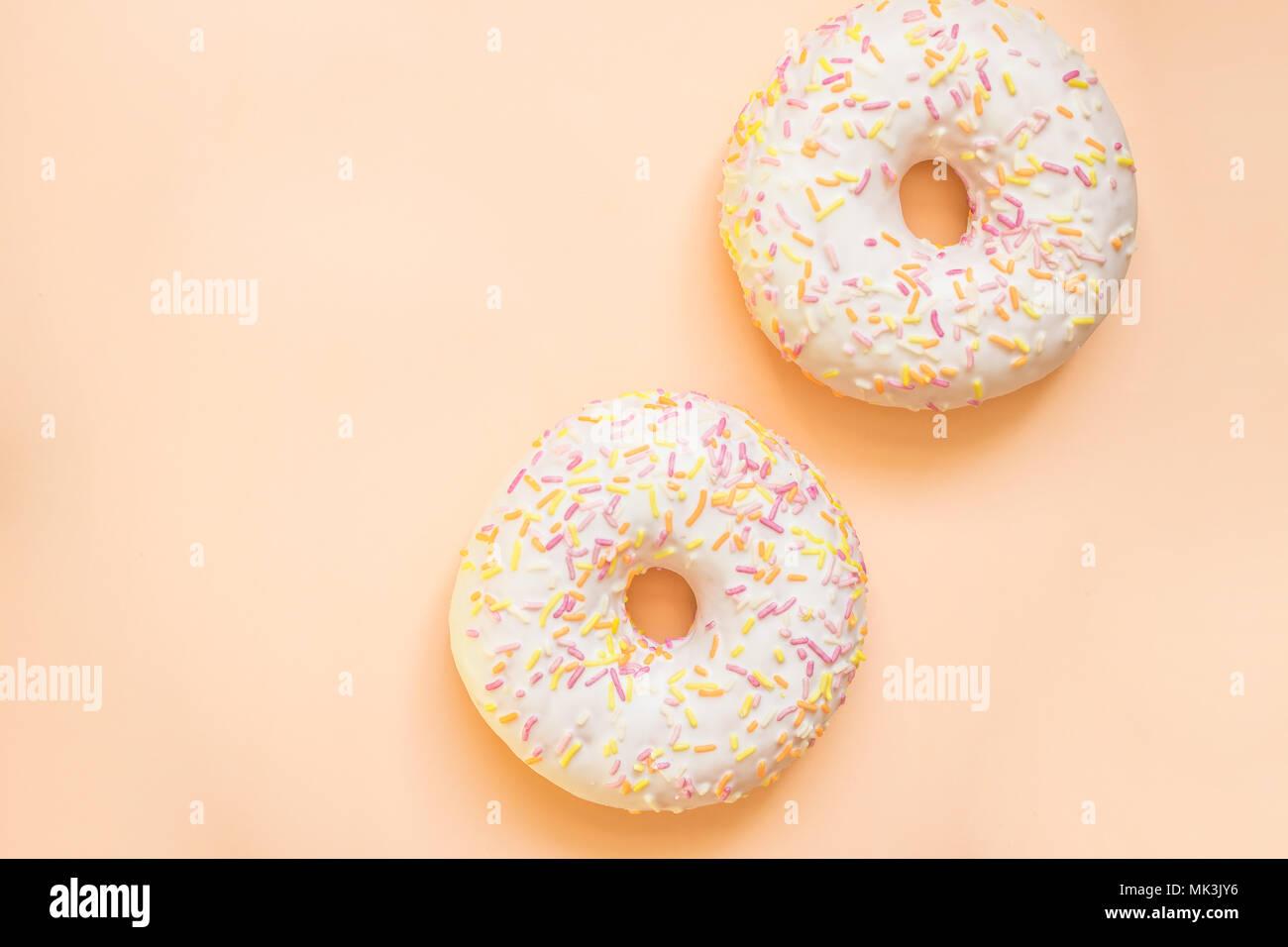 Donut mit weißer Zuckerglasur farbige Topping, auf gelben Hintergrund isoliert. Lecker Klassiker zwei verglaste Donuts isoliert. Leckere bunte Donuts Stockbild