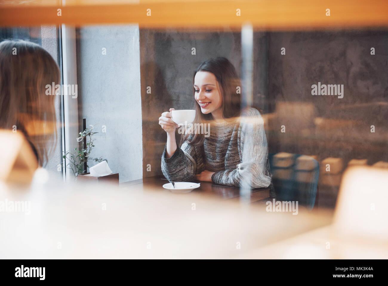 Zwei Freunde Kaffee zusammen in einem Café, als sie an einem Tisch sitzen plaudernd Stockbild