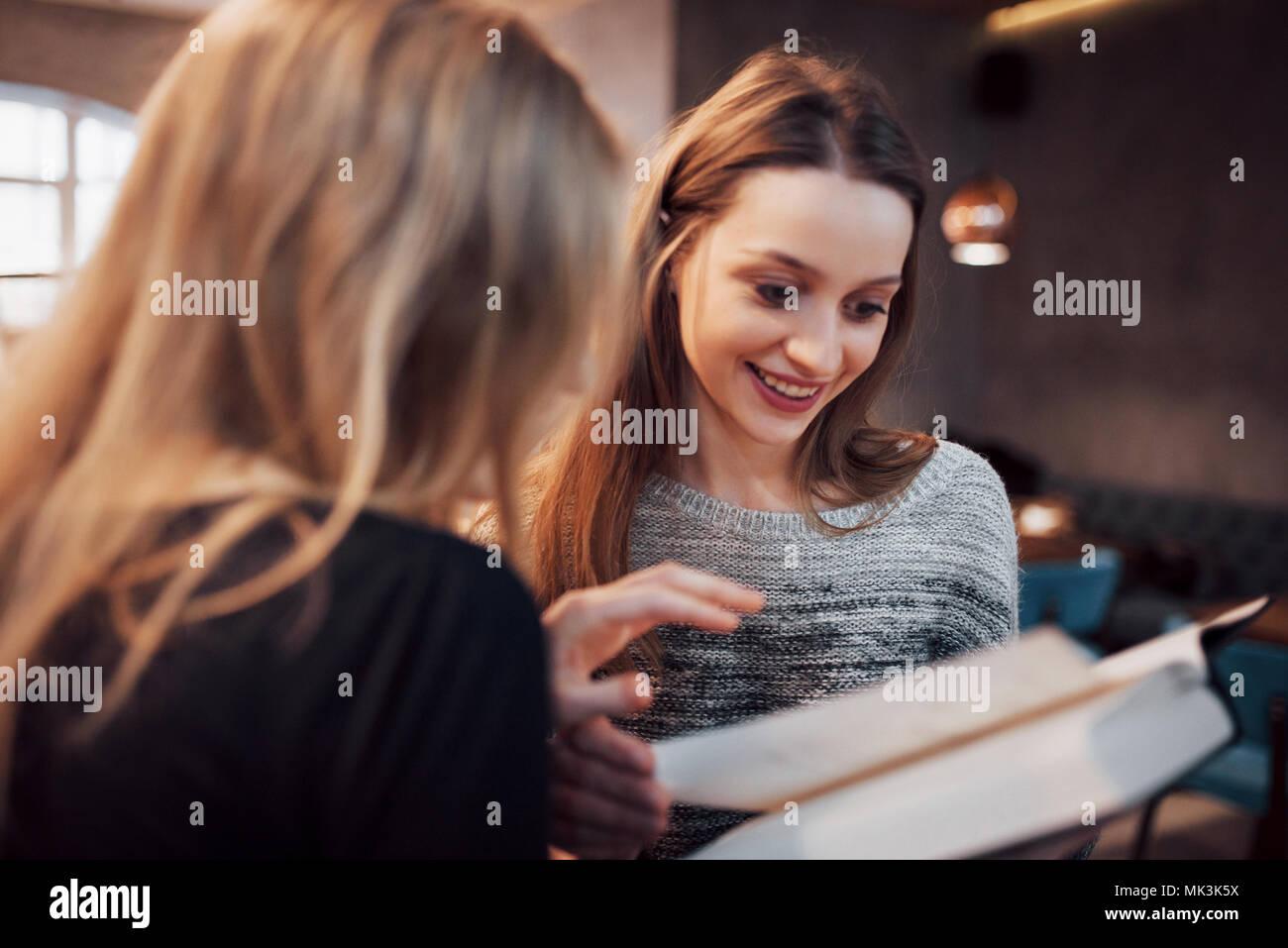 Zwei Mädchen, die in der Lesung buchen Sie während der Pause im Cafe absorbiert. Süße schöne junge Frauen lesen und Kaffee trinken Stockbild