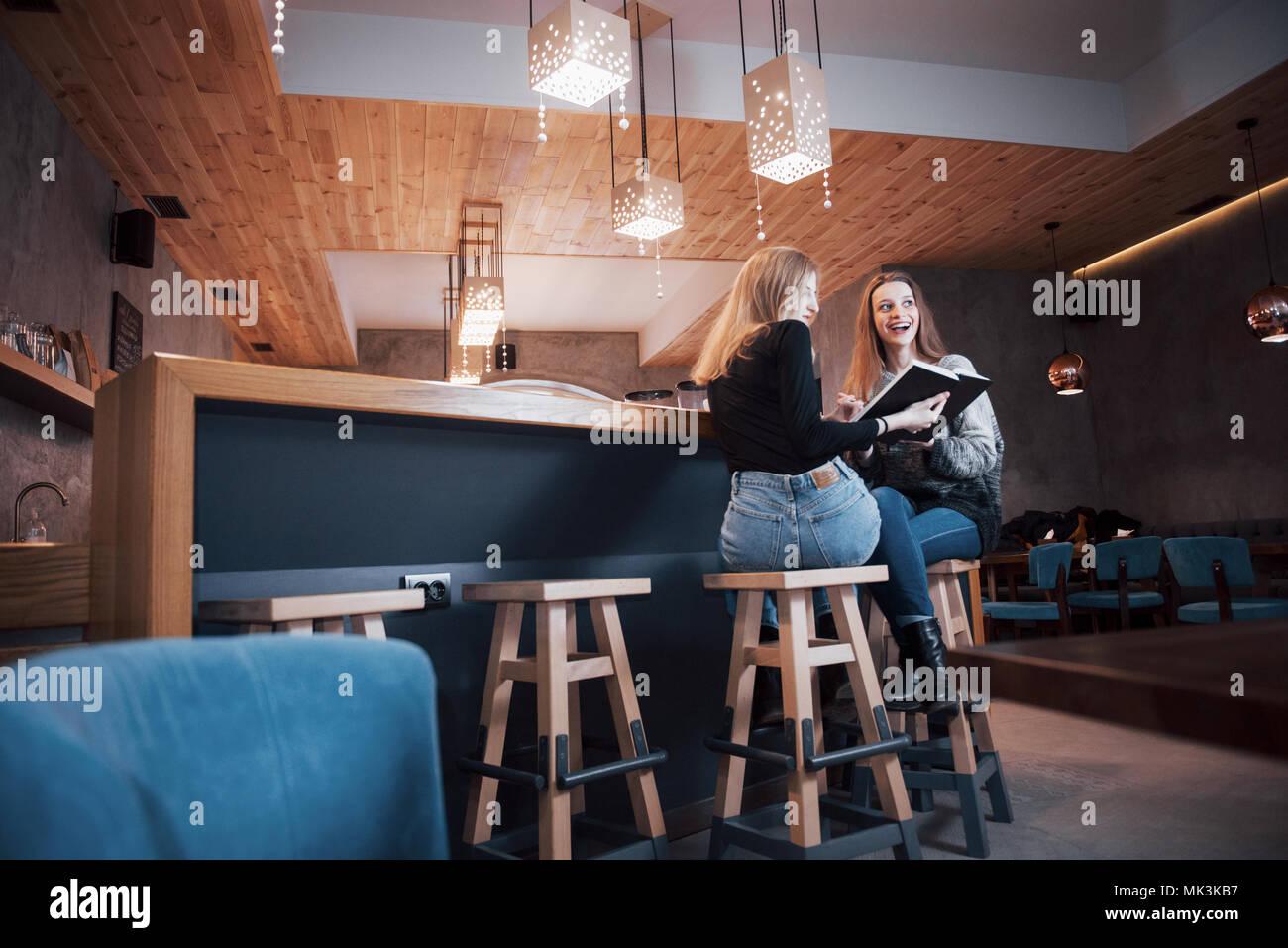 Zwei junge Frauen sitzen im Cafe Kaffee trinken und genießen in gute Bücher. Studenten auf Kaffeepause. Bildung, Lifestyle Konzept Stockbild