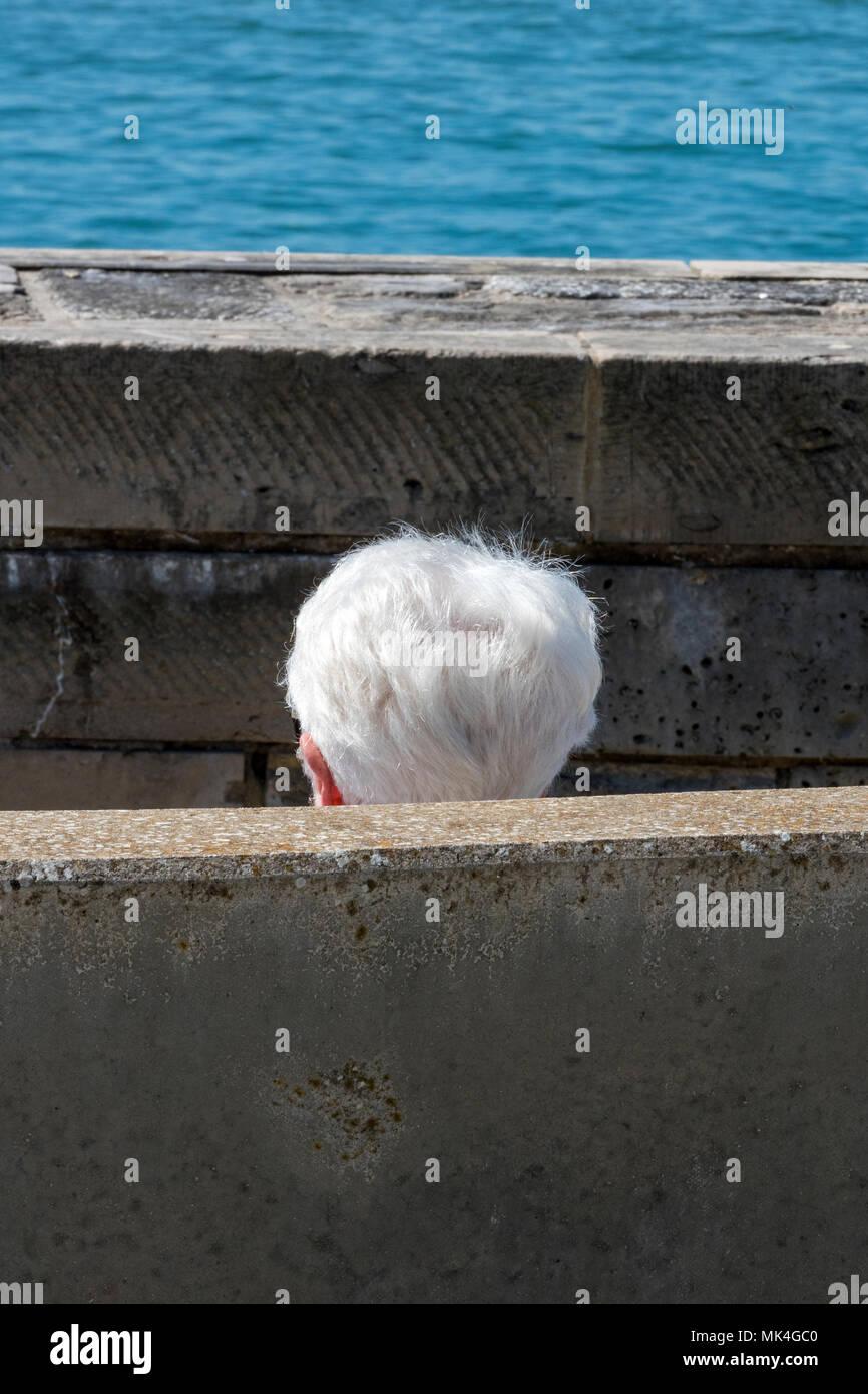 Eine ältere Person mit silbernen oder grauen weißes Haar sitzt hinter einer Wand am Meer mit nur ihren Kopf angezeigt. Alternde Person weiß Silber. Stockbild