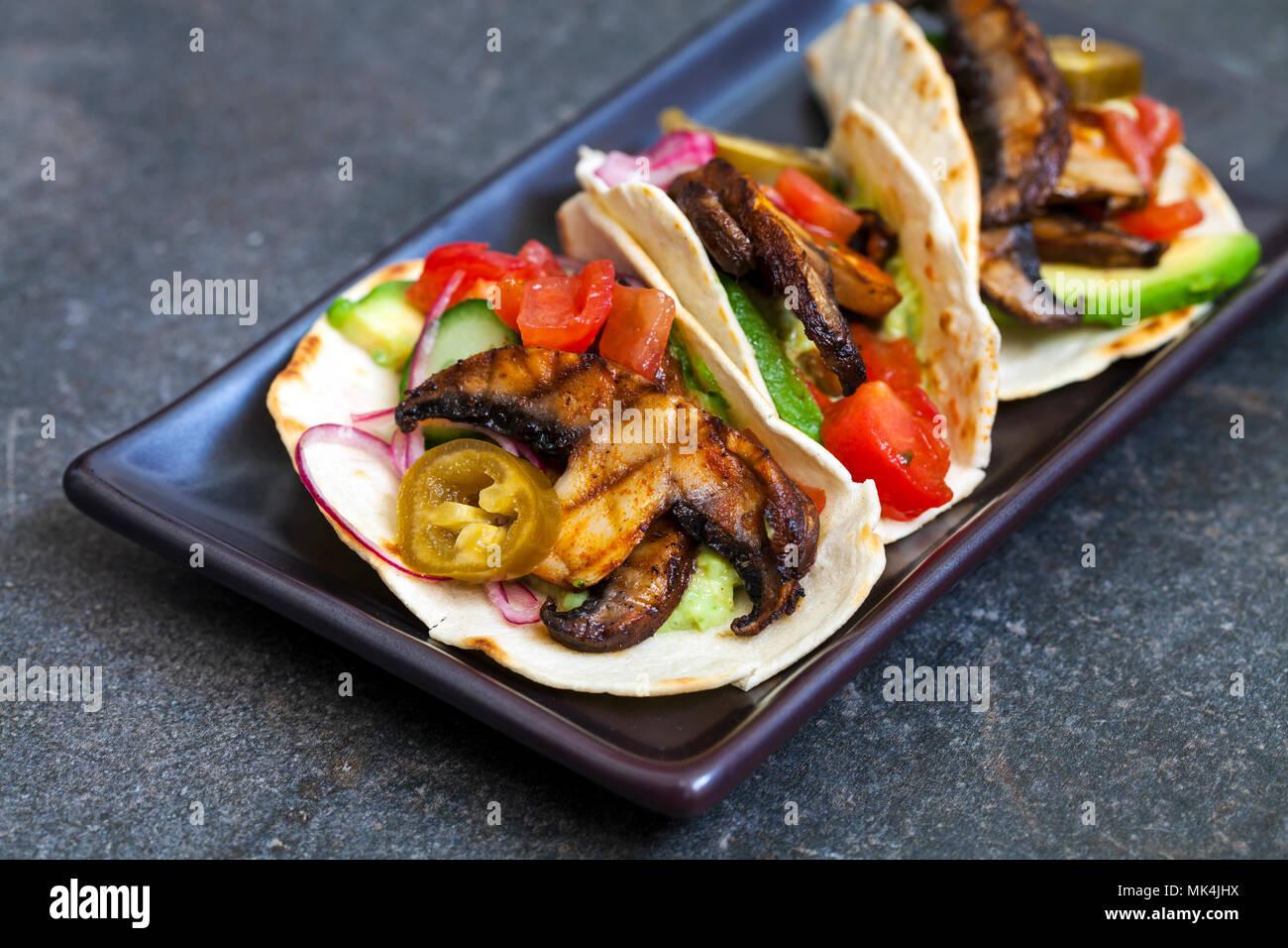 Veganen Tortillas mit Pilzen, Avocado, eingelegte Zwiebeln und Gurken Stockbild