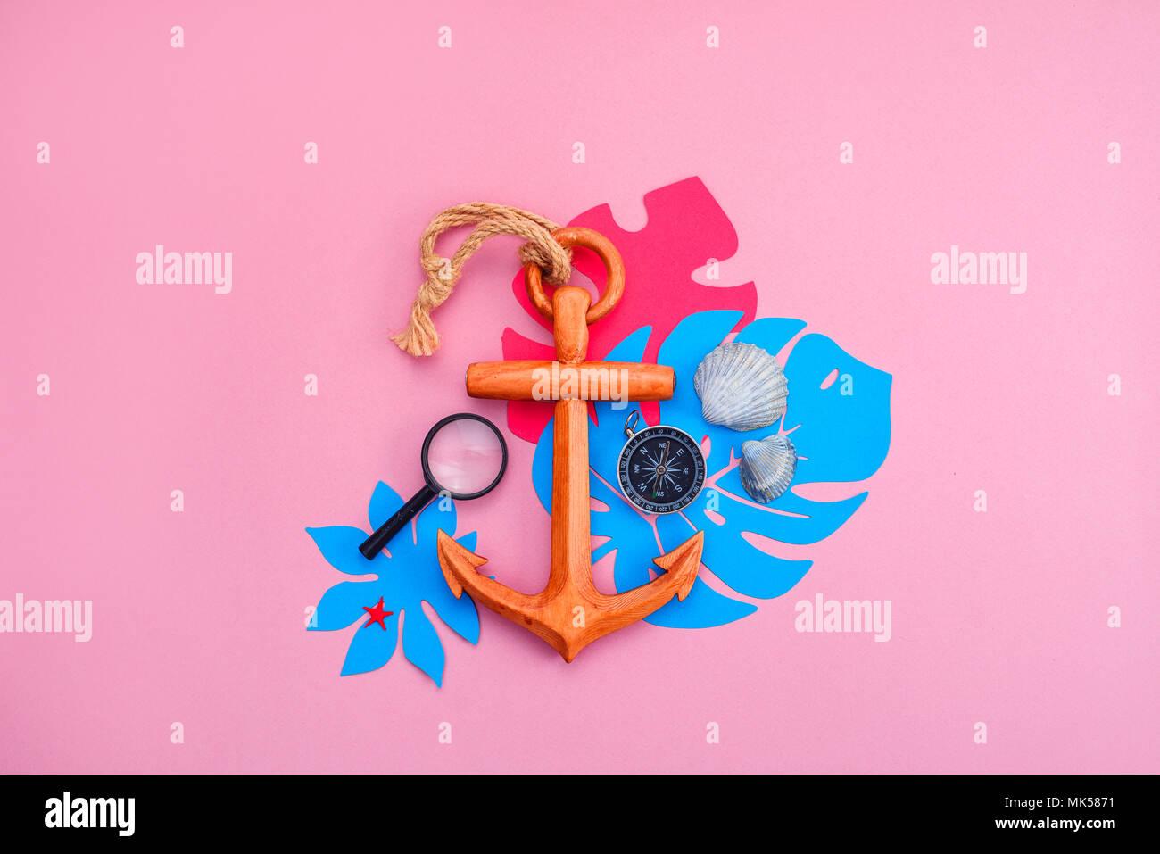 Bunte Reise und Konzept auf einem hellen Rosa Hintergrund. Tropische Blätter, Holz- Anker, Kompass und Muscheln mit kopieren. Stockbild