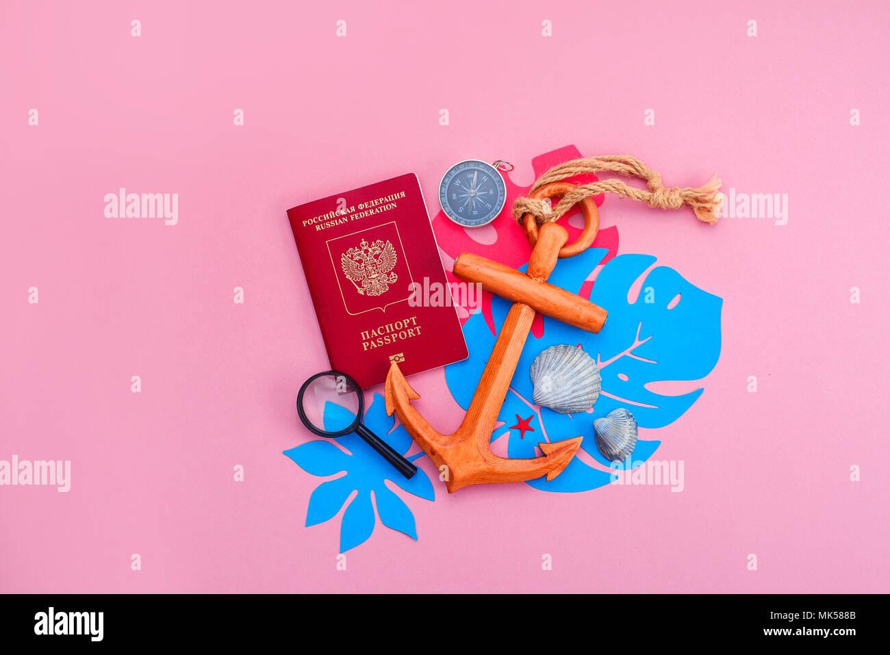 Bunte Reise und Konzept auf einem hellen Rosa Hintergrund. Tropische Blätter, Holz- Anker, Reisepass, Kompass und Muscheln mit kopieren. Stockbild