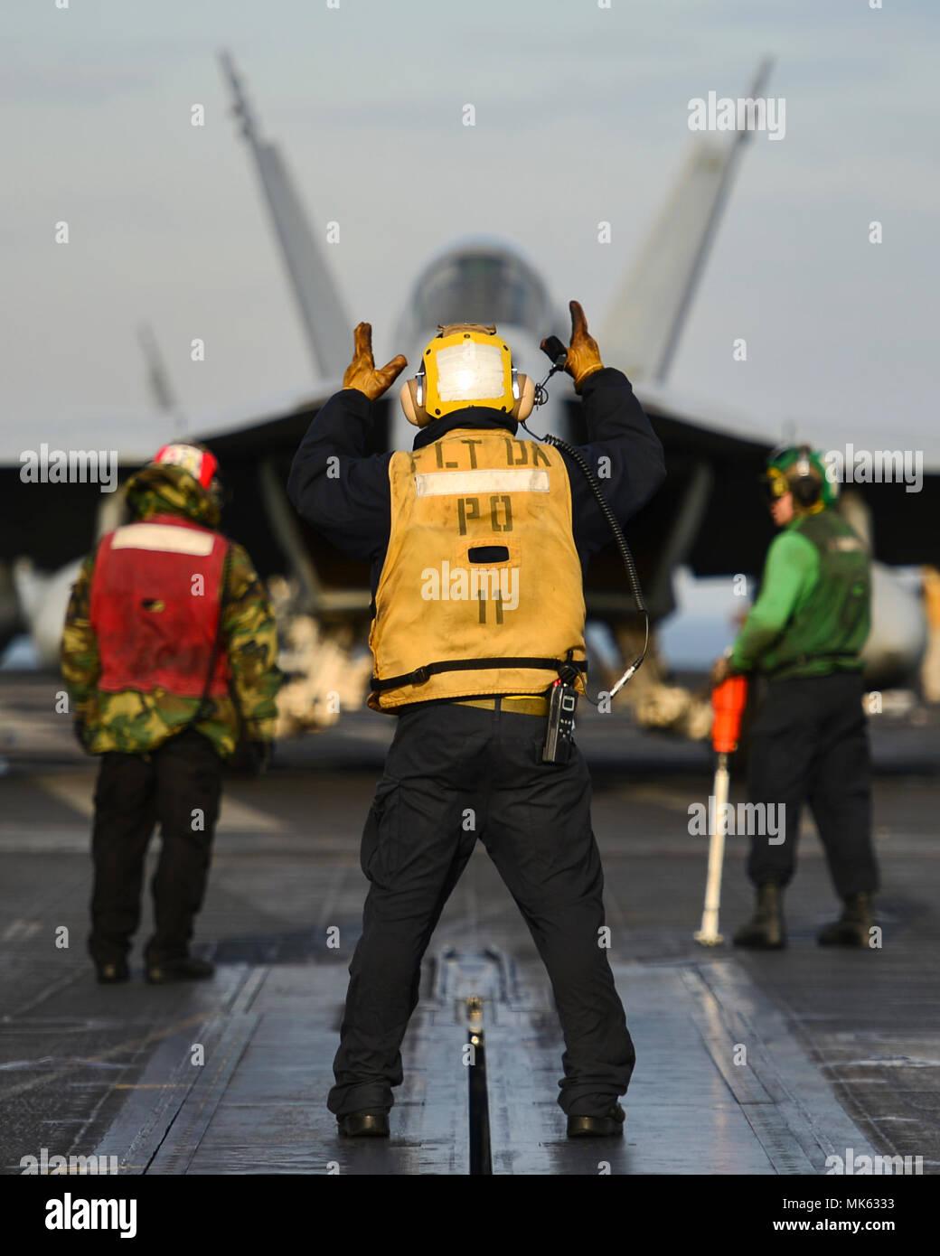 171113-N-JH 929-115 WESTERN PACIFIC (Nov. 13, 2017) Segler Durchführung Flugbetrieb auf dem Flugdeck an Bord der Flugzeugträger USS Nimitz (CVN 68). Der Nimitz Carrier Strike Group ist in regelmäßigen Bereitstellung in den USA 7 Flotte Bereich für Maßnahmen zur Erhöhung der Sicherheit des Seeverkehrs und Theater Sicherheit Bemühungen um Zusammenarbeit. Der US-Pazifikflotte hat den Indopazifischen routinemäßig für mehr als 70 Jahre patrouillierten die regionale Sicherheit, Stabilität und Wohlstand. (U.S. Marine Foto von Mass Communication Specialist 3. Klasse Cole Schroeder/Freigegeben) Stockfoto